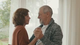 Happy senior couple relaxing at home, dancing. Slow motion