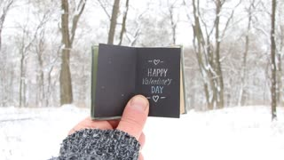 Happy Valentines Day idea, male holding a retro book with the inscription