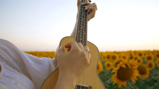 Happy woman in sunflower field playing on ukulele and singing. Summer girl in cowboy straw hat. Caucasian young lady have fun. Slow motion. Little guitar. music concept