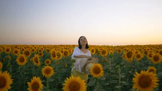 Happy woman in sunflower field. Summer girl in flower field cheerful and joyful. Caucasian young lady throws hat up with arms raised up. Slow motion