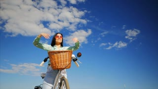 Happy young girl enjoying the sun sitting on a white vintage bicycle with basket. Hands up to the sky. Freedom concept. Carefree brunette girl. Slow motion.
