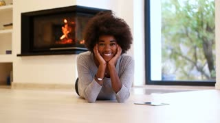 Happy Young Woman Relaxing beside fireplace