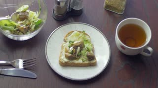 Healthy morning sandwich and a cup of tea on the desktop at home. Man having a breakfast made from bread, lettuce and mushrooms.