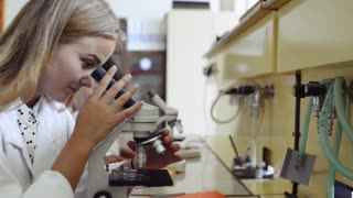 High school student with microscope in laboratory.