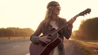 hippie girl plays guitar. portrait of a young girl wearing sunglasses at dawn