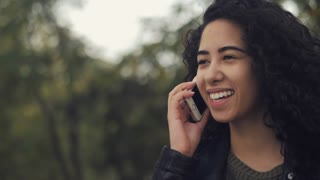 Hispanic brunette girl with curly hair talking on the phone, smiling happy beautiful woman have conversation with friend on smartphone in the autumn street. Slow motion