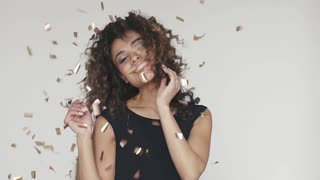 hispanic woman celebrating party with sparkling dancing gold glitter background. concept of the holiday, fun, celebrate. slow motion