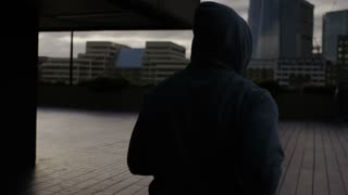 Hooded male jogger soaks in the view of the city in the morning sun, in slow motion