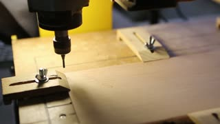 In the woodworkers shop the cnc drill is drilling  on the wooden plank