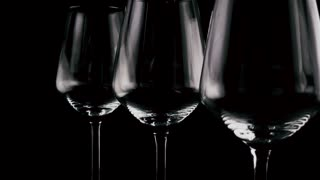 In three identical glasses are poured simultaneously wine, red white pink on a black background, focus on red. Slow motion