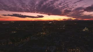 Incredible and amazing extreme long shot aerial drone view of metropolis or big european city, with old buildings, cars moving in highways and narrow street, at dusk or dawn with colorful skies