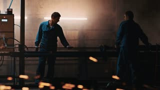 Industrial employees using inversion heater for metal piece in production hall