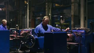 Industrial employees working on automatic turning lathe and metalworking machine