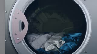 Industrial washing machine. Close up of washing machine loading clothes. Industrial uniform washing. Pharmaceutical factory worker loading industrial washing machine with industry uniform