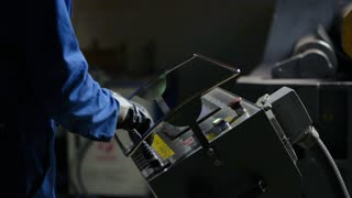 Industrial worker using electronic computer equipment for bending metal plate