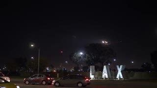 Jet airplane landing in Los Angeles with LAX airport sign at night with cars and traffic