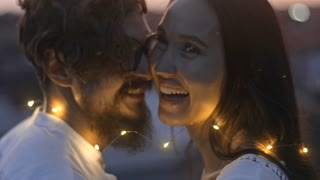 Joyous young couple wrapped in fairy lights smiling and laughing while talking face to face on rooftop