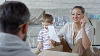 Laughing young woman sitting on floor of new apartment and looking at furniture assembling manual, then discussing it with husband showing her wooden pieces; cute little boy sitting beside