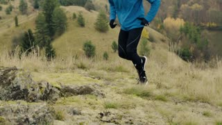 Legs of unrecognizable man in blue jacket running in autumn nature