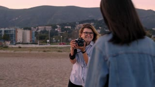 Lifestyle photographer, blondie girl, takes photos of attractive brunette model, talks with her and show how to pose in camera on empty sand beach at golden sunset hour