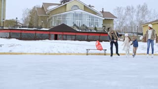 Lockdown of happy family with two children wearing warm clothing and ice skating together on outdoor rink in winter