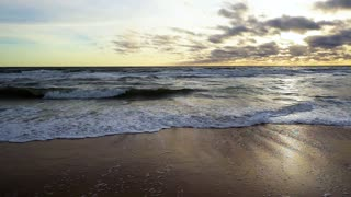 Long waves roll on a sandy beach in the evening in a troubled ocean in the setting sun slow mo