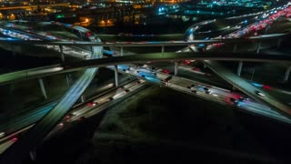 Los Angeles urban aerial drone time-lapse in motion or hyperlapse at night flying towards an interstate with traffic showing the on and off ramp circles indicative of the fast futuristic city lifestyle