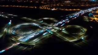 Los Angeles urban aerial drone time lapse in motion or hyperlapse at night flying towards an interstate with traffic showing the on and off ramp traffic circles.