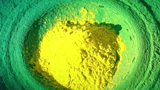 Loudspeaker throws yellow and green powder in the air, super slow motion shot. Music, Brazil, festival or party concepts
