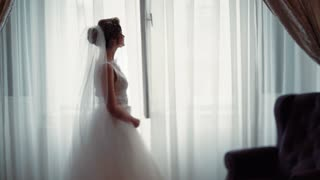 Lovely bride in a gorgeous white wedding dress and veil standing near the window, waiting for her bridegroom. Best moment, romantic atmosphere, feeling happy. Cozy light