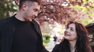Lovely young couple in love walking down the blossoming cherry trees alley, embracing and talking to each other. Girl has a flower in her hair. Romantic date, true feelings, real emotions