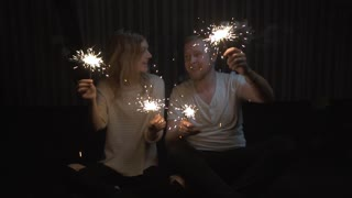 lovers boy and girl with sparklers in hands having fun and kissing. slow motion