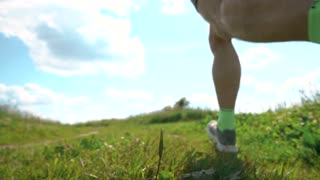 Low angle super slow motion shot of a defocused male athletic runner, back view