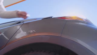 Low angle view of driver opening fuel cap and inserting nozzle into car tank; sunlight shining at camera