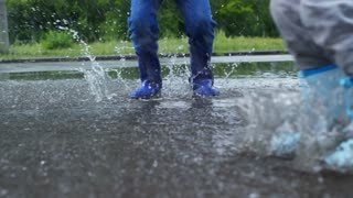 Low section with slow motion of legs of children in rubber boots jumping in puddle during rain
