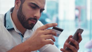 Luxurious young man in a café, uses his phone and credit cards for online shopping. Modern technologies, being online. Shopping online. Close up view, camera stabilizer shot.