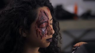 Make-up artist make the girl halloween make upin studio. Halloween face art. Woman applies on professional greasepaint on the face of spanish girl. War-paint with blood, scars and wounds. Slow motion