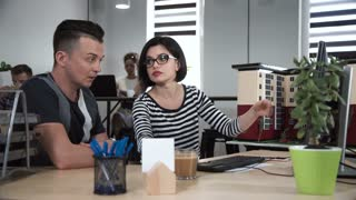 Man and woman architects discussing in front of computer in office new layout of building