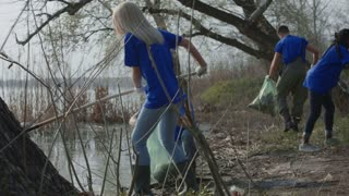 Man and woman in t-shirts of volunteer community taking care of forest ecology cleaning up trash on pond.