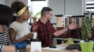 Man discussing with two co-worker women in office