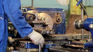 Man employee machine operator controlling metalworking details and parts