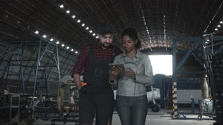 Man go and discussing over digital tablet in aircraft hangar with black woman