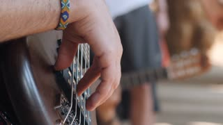 man playing the bass guitar at the concert in the street. Close up view of guitarist plays on brown wooden musical instrument. Street musician with a wicker hippie bracelet on his arm. Slow motion