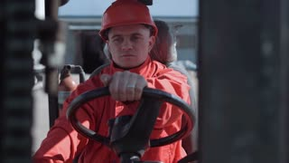 Man wearing bright red uniform driving the loader near the warehouse outdoor