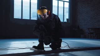 Man wearing protective head mask cutting metal with angle grinder