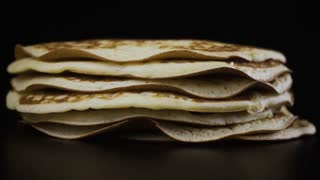 Maple syrup flows in a thin trickle on a pile of pancakes. Slow motion