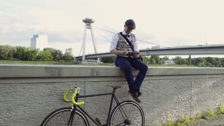 Mature businessman with tablet and bicycle at the river.