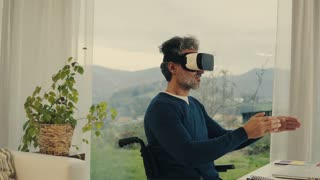 Mature man in wheelchair with VR goggles working in home office