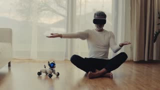 Mature man with VR goggles and robot smart dog at home, sitting on the floor. Slow motion