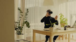 Mature man with VR goggles working in home office